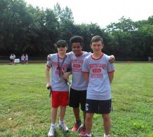 Three Friends Pose Together while participating in Track and Field Event During Sports Camp
