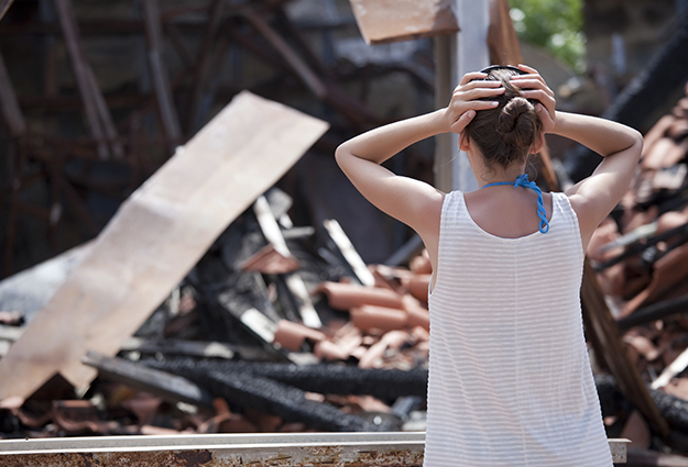 Girl Standing In Front Of A House Destroyed By A Tornado.